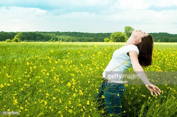 Woman enjoying nature in mustard field, horizontal with copy space.