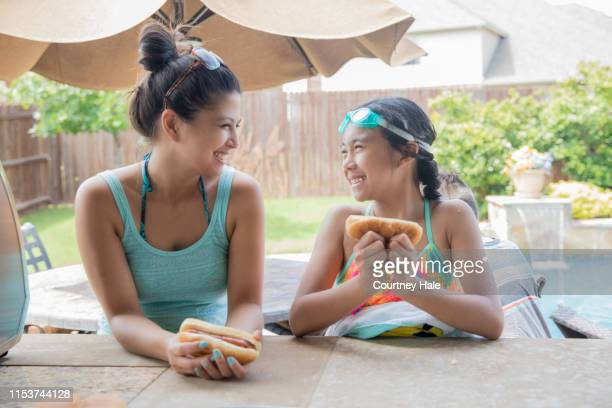 woman enjoying neighborhood cookout with her elementary age daughter - filipino family dinner stock pictures, royalty-free photos & images