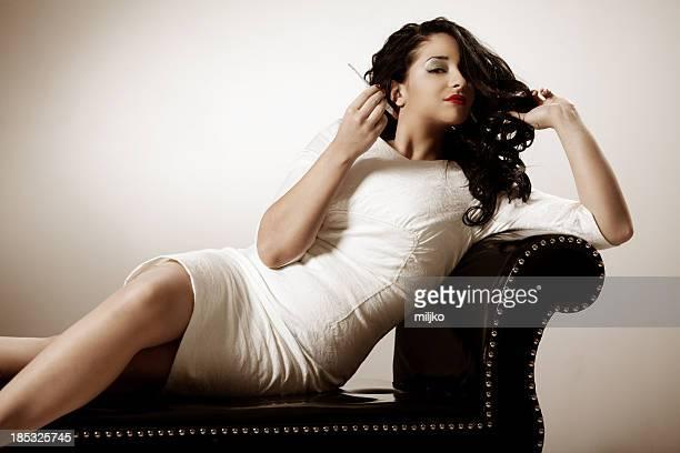 Woman enjoying on the sofa and smoking cigarette