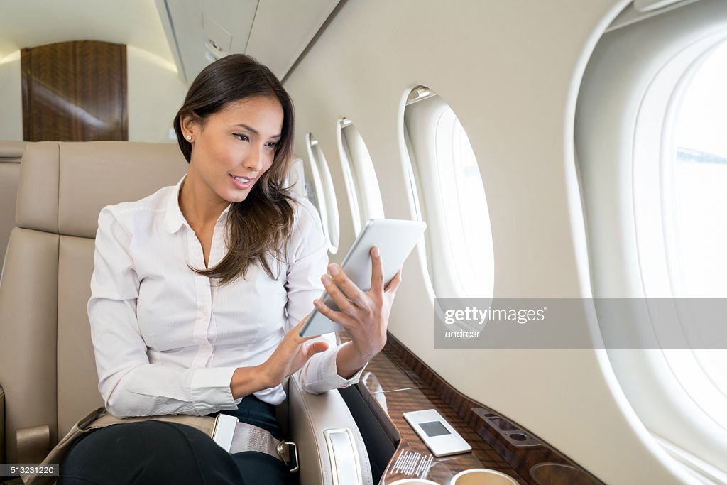 Woman enjoying onboard entertainment in her tablet computer : Stock Photo
