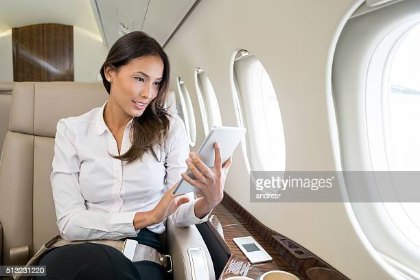 woman enjoying onboard entertainment in her tablet computer - celebrities photos stock pictures, royalty-free photos & images