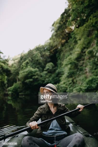 Woman enjoying paddling inflatable raft on river