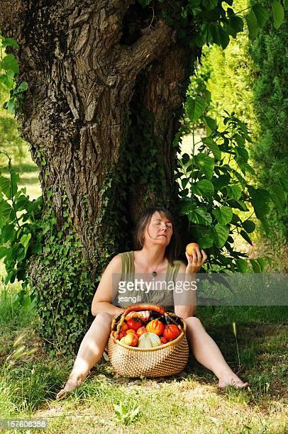 Woman enjoying peach in orchard