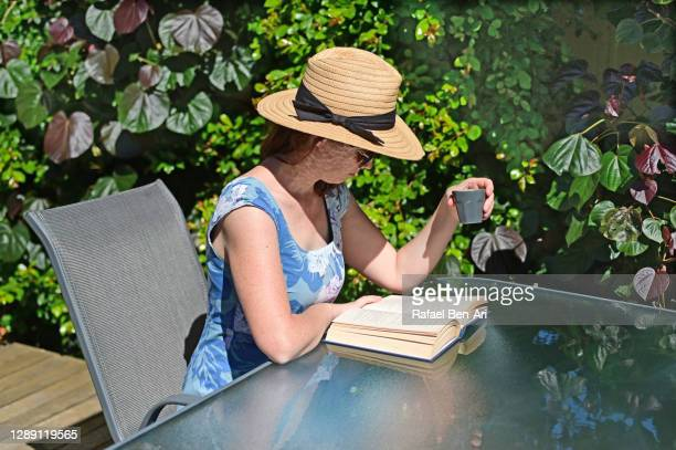 woman enjoying reading a book in the garden - rafael ben ari stockfoto's en -beelden