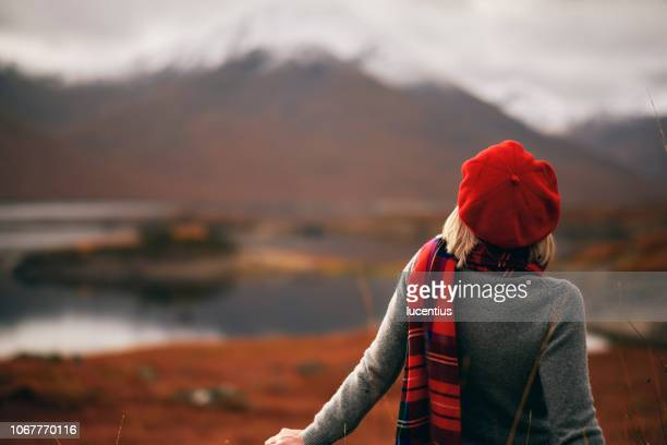 woman enjoying retirement in scotland highlands - red hat stock pictures, royalty-free photos & images