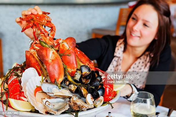 Woman enjoying seafood at Rick Stein restaurant, Padstow