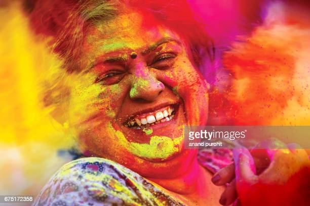 Woman enjoying showers of colours during Holi festival, India