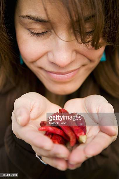 Woman enjoying smell of chili peppers