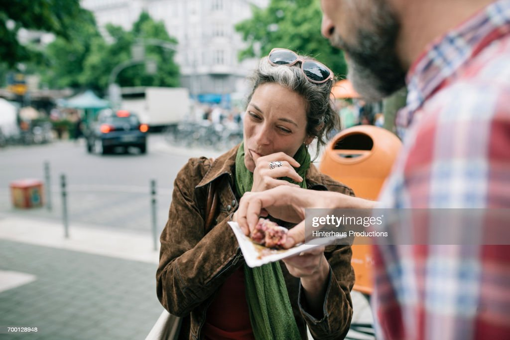 A Woman Enjoying Streetfood With Her Partner : Stock Photo