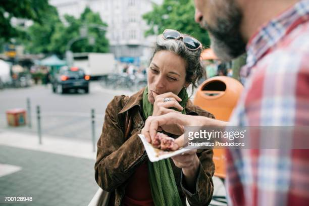 a woman enjoying streetfood with her partner - man eating woman out - fotografias e filmes do acervo
