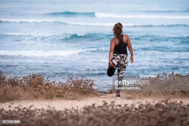 woman enjoying stretching her leg outdoors. - fat woman at beach stock photos and pictures
