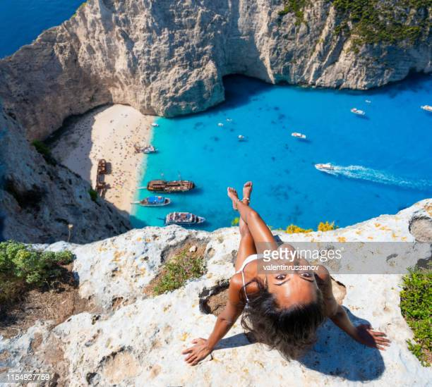 woman enjoying summer beach vacations in zakynthos greece navagio beach - butlins stock pictures, royalty-free photos & images