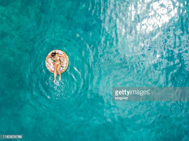 woman enjoying summer - floating on water stock pictures, royalty-free photos & images