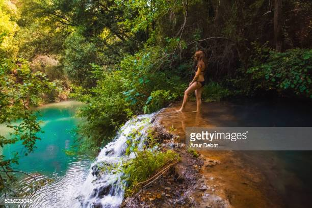Woman enjoying summer time in the beautiful river with natural pools cooling off from the hot days during travel vacations in the Catalonia region.