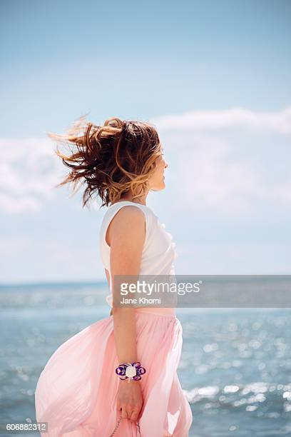 woman enjoying summer vacation - skirt blowing stock photos and pictures