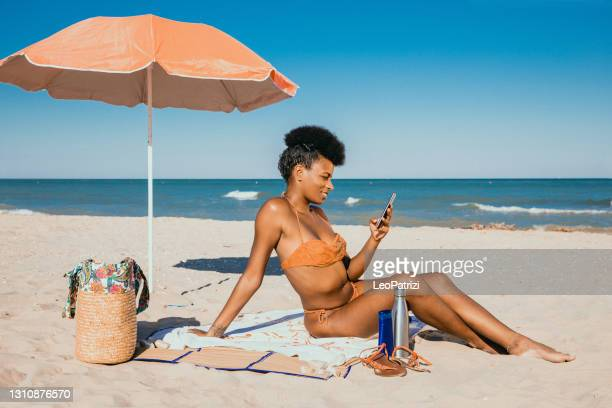 woman enjoying summertime at the beach - sunbathing stock pictures, royalty-free photos & images