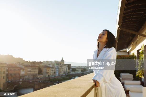 woman enjoying sun on hotel balcony, florence, toscana, italy - balcony stock pictures, royalty-free photos & images