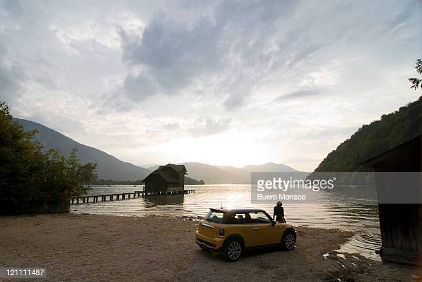 woman enjoying sunset at lake with car - landfahrzeug stock-fotos und bilder
