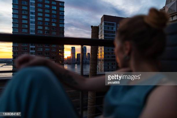 woman enjoying sunset on a terrace in new york: view on jersey city - manhattan new york city stock pictures, royalty-free photos & images