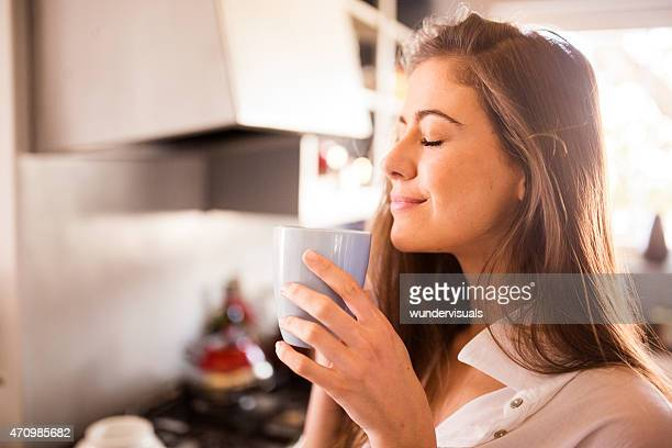 Woman enjoying the aroma of her cup of coffee