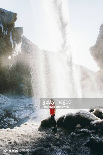 woman enjoying the bright sunset behind the waterfall in iceland - behind waterfall stock pictures, royalty-free photos & images