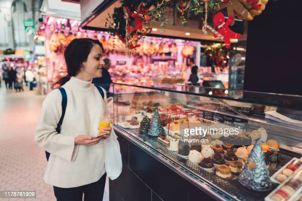 frau genießt die kuchenthekaufausstellung auf dem bauernmarkt - auslage stock-fotos und bilder