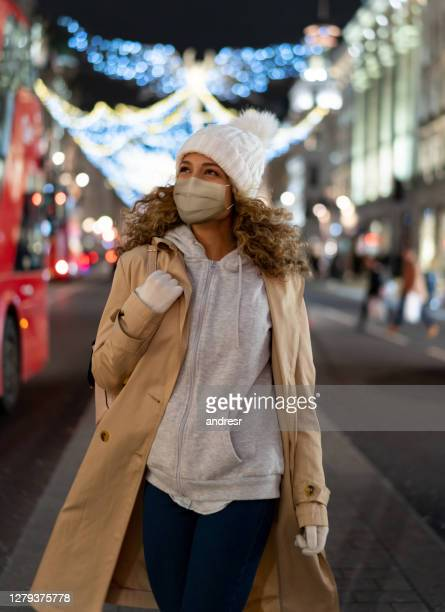 woman enjoying the christmas lights in the city while walking on the street wearing a facemask - coronavirus winter stock pictures, royalty-free photos & images