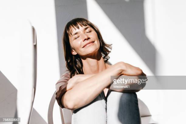 woman enjoying the sun with closed eyes - hot older women stock pictures, royalty-free photos & images