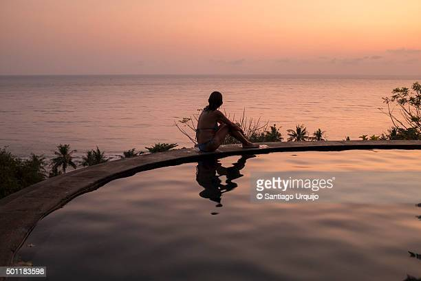 Woman enjoying the sunset from the edge of a swimming pool