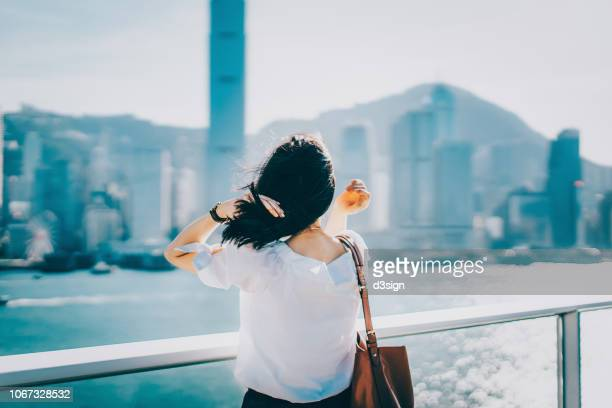 woman enjoying the tranquility and gentle wind breeze by the harbour in the city - 雰囲気 ストックフォトと画像