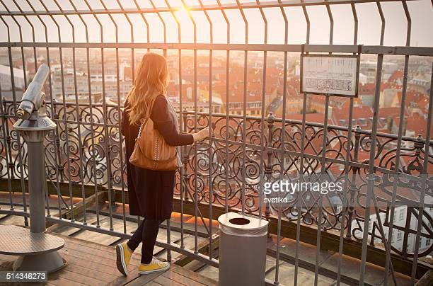 Femme profitant de la vue sur le coucher du soleil.