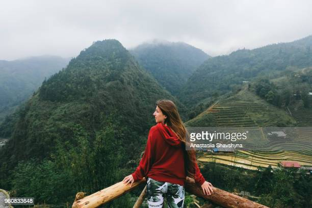 woman enjoying the view of foggy rice terraces in sa pa, vietnam - sa pa stock photos and pictures