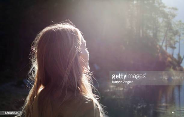 woman enjoying the view of stunning lake eibsee, bavaria, germany - sunlight stock-fotos und bilder