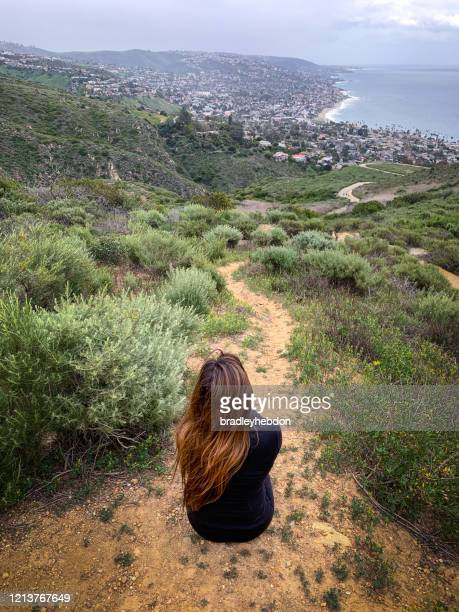 woman enjoying view from dartmoor trail in laguna beach, ca - laguna beach california stock pictures, royalty-free photos & images