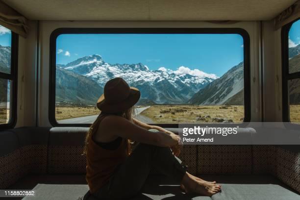 woman enjoying view from inside motorhome, wanaka, taranaki, new zealand - fugir da realidade imagens e fotografias de stock