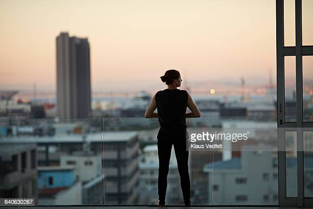 Woman enjoying view from penthouse apartment