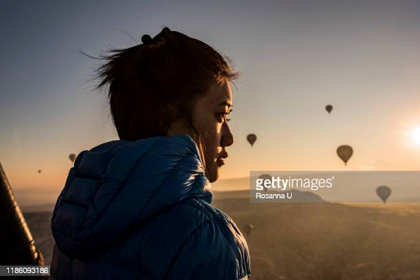 woman enjoying view, hot air balloons flying in background, göreme, cappadocia, nevsehir, turkey - turkey middle east stock pictures, royalty-free photos & images