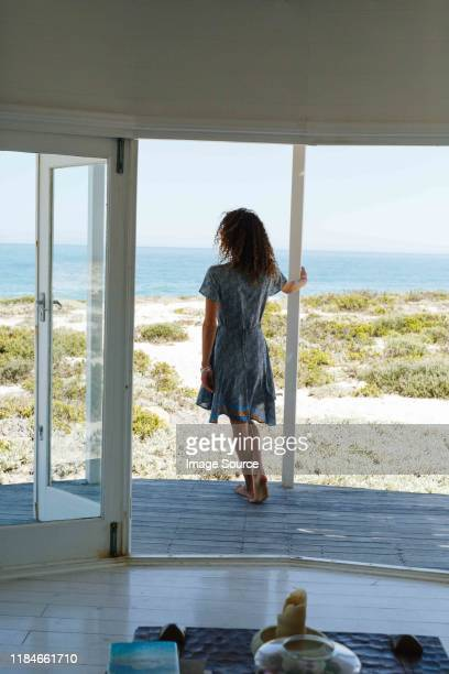 woman enjoying view of sea on porch of beach house - holiday villa stock pictures, royalty-free photos & images