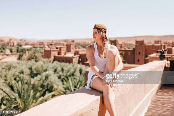 woman enjoying view on stonewall, ouarzazate, souss-massa-draa, morocco - femme marocaine photos et images de collection
