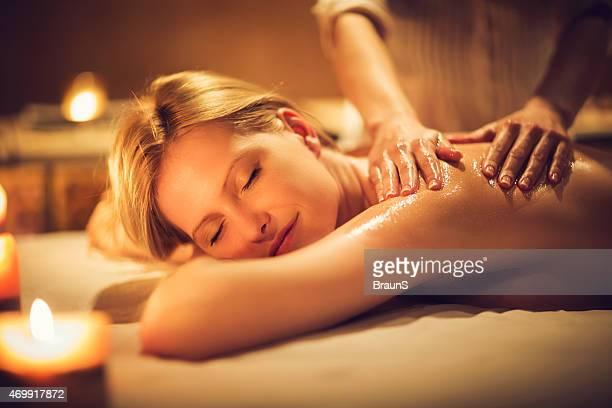 Mujer disfrutando mientras reciben respaldo una sesión de masajes en el spa.