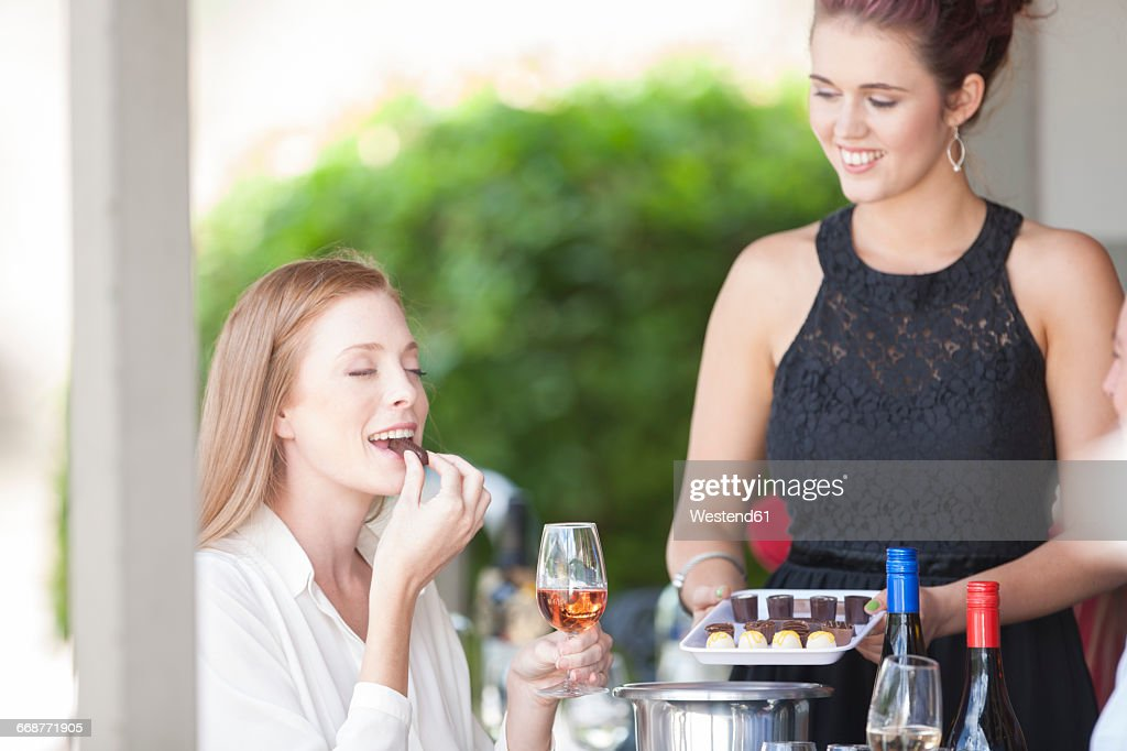 Woman enjoying wine and chocolates served in restaurant : Stock Photo