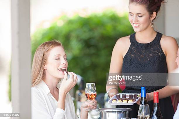 Woman enjoying wine and chocolates served in restaurant
