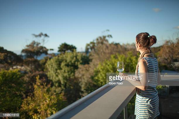 Woman enjoying wine and view from balcony