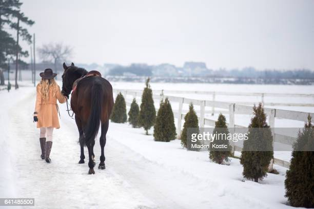 Woman enjoying winter breaks with her horse
