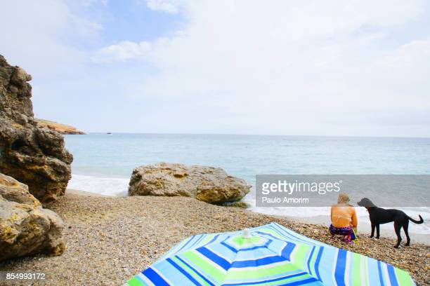 A woman enjoying with her dog at beach in France