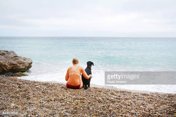 A woman enjoying with her dog on the beach