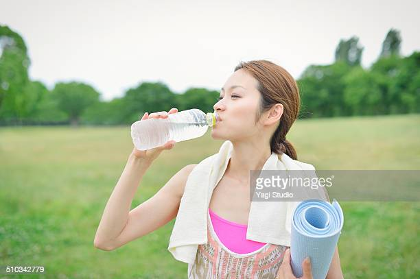 woman enjoying yoga in park - 飲料水 ストックフォトと画像