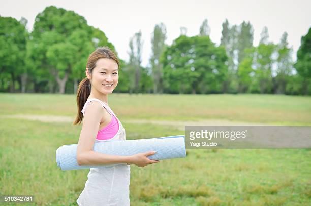 woman enjoying yoga in park - エクササイズマット ストックフォトと画像