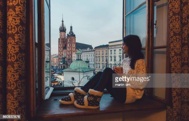 woman enjoyng krakow city from the window - lazy poland stock photos and pictures