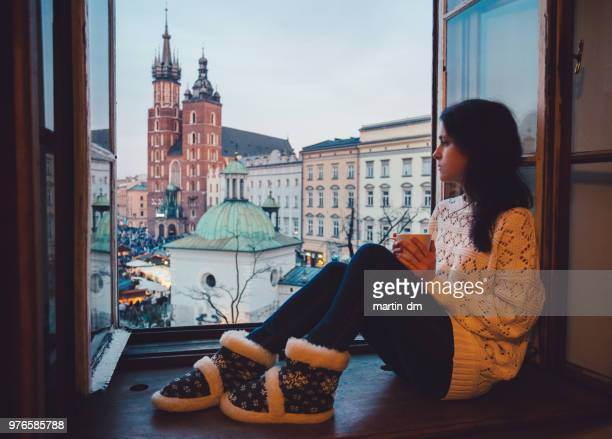 woman enjoyng krakow city from the window - hostel stock pictures, royalty-free photos & images
